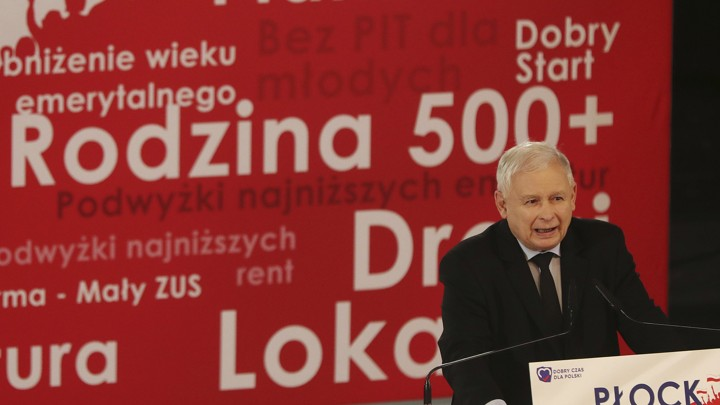 Jaroslaw Kaczyński, the leader of Poland's governing party, stands at a lectern in front of a banner with his party's policies.