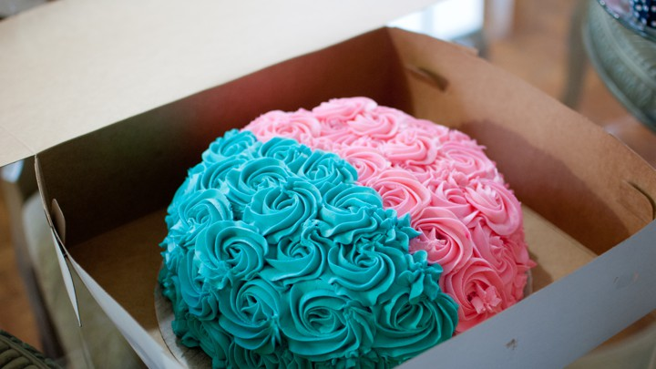 A cake frosted in two colors: one half blue, the other half pink