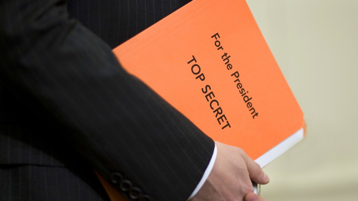 A White House staffer holds a folder with top-secret documents.