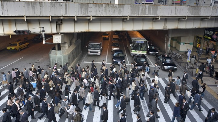 Workers cross the street in Osaka, Japan.