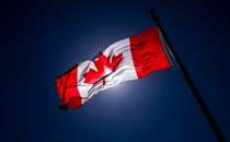 A Canadian flag, slightly darkened by the light, waves in the air.