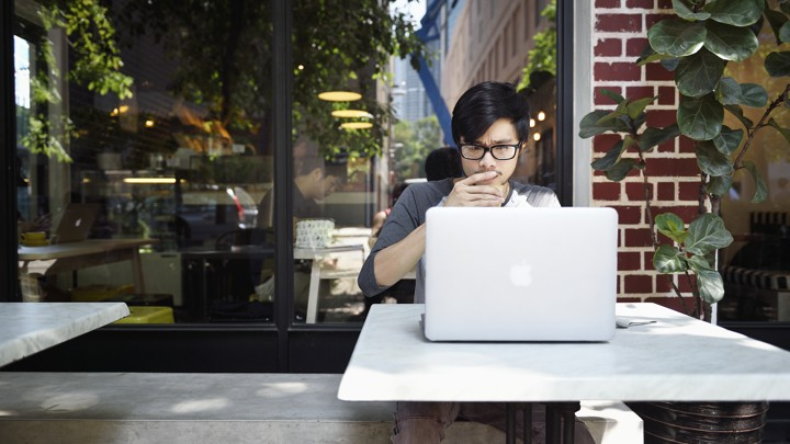 A young man looks thoughtfully at a laptop while sitting at a cafe