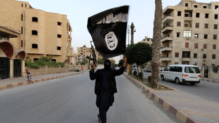 A man walks down a street holding an ISIS flag and a gun in Raqqa.
