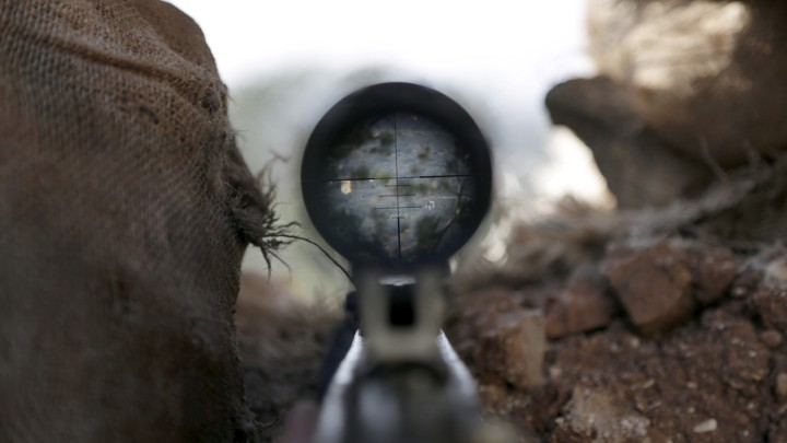 A view is seen through the scope of a weapon in the northwestern Syrian city of Idlib.