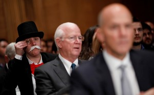 A monocle-wearing spectator looks on as Richard Smith, the former chairman and CEO of Equifax, testifies before the U.S. Senate Banking Committee.