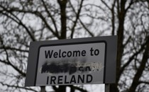 """A sign that reads """"Welcome to Northern Ireland"""" with the word """"Northern"""" scratched out."""