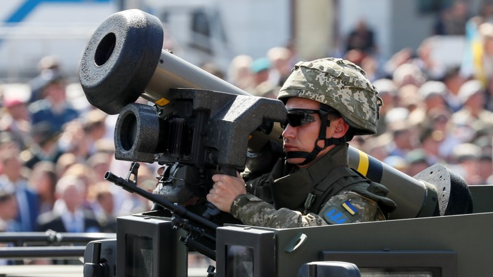 A Ukrainian army service member rides in an armored vehicle with a Javelin anti-tank missile during a parade to celebrate Ukraine's independence.