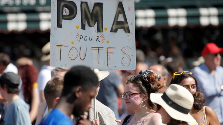 "A participant in the Paris gay pride parade holds up a placard which reads ""PMA (Fertility treatment) for all."""