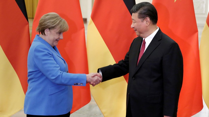 Angela Merkel and Xi Jinping shake hands at the Great Hall of the People in Beijing.