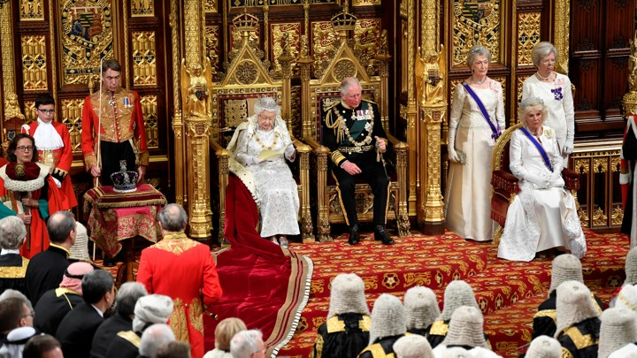 Queen Elizabeth and Prince Charles sit on golden thrones, surrounded by members of Parliament and other officials in both formal and official attire..