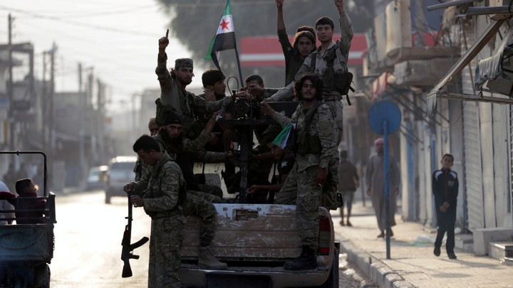 Syrian rebel fighters at the back of a truck