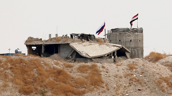 Russian and Syrian national flags are raised above a structure.