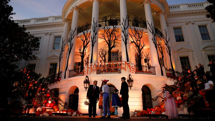 Trump passes out candy in front of a halloween-decorated White House.