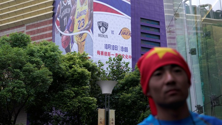 A man with his head wrapped in a Chinese national flag is seen near a building with a partly removed banner advertising an NBA game in Shanghai.