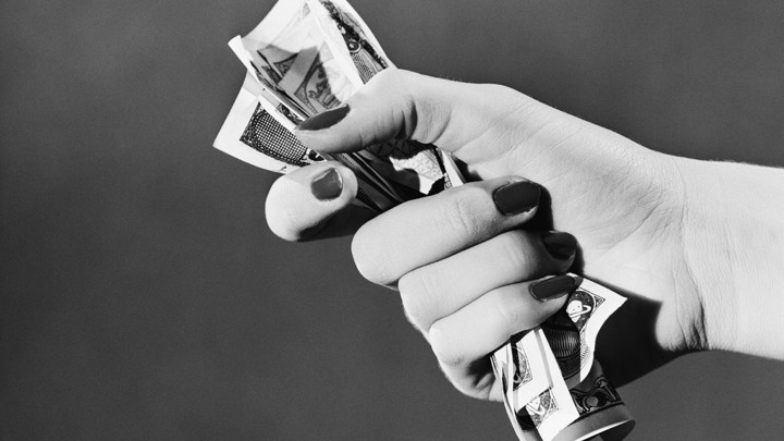 Woman holding fist full of cash