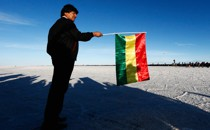 Evo Morales gets ready to wave a Bolivian flag to start the race during day eight of the Dakar Rally on the Salar de Uyuni.