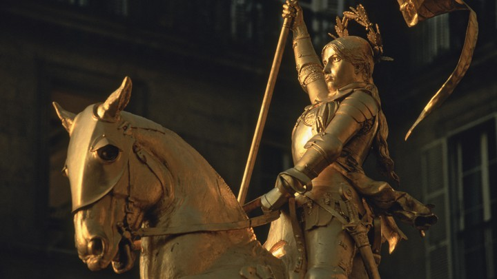 A golden statue of Joan of Arc looking defiant on her horse.