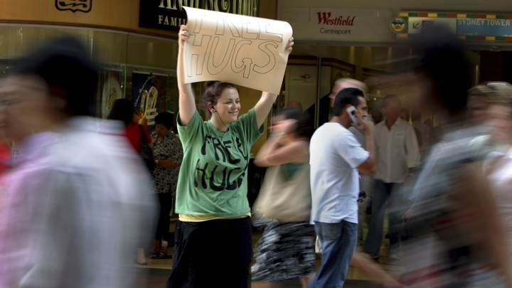 """Woman holding """"Free Hugs"""" sign"""