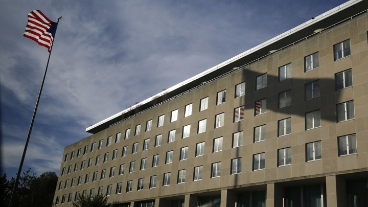 The U.S. flag and its shadow falling on the Harry S. Truman Building at the Department of State