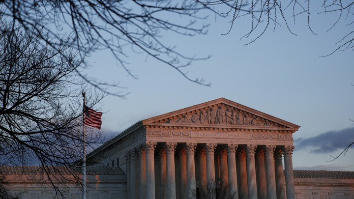 The Supreme Court (and American flag next to it) are slightly pink in a sunset, and framed by leaf-less trees.