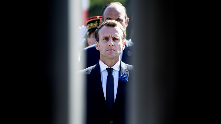 Emmanuel Macron stands framed between two doors with people lined up behind him.