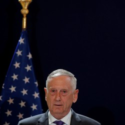 James Mattis stands in front of a black background and an American flag.