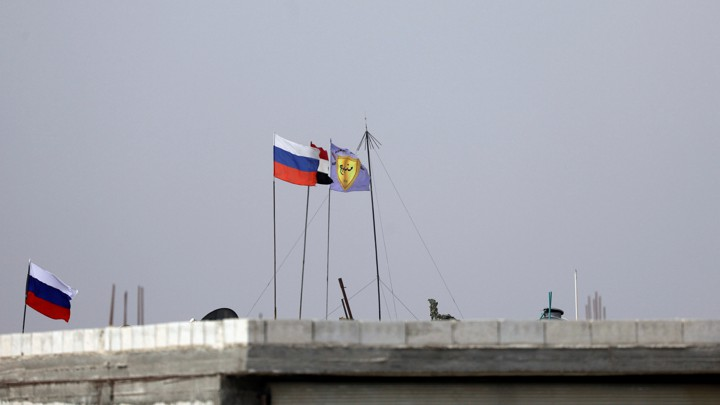 Russian, Syrian and Manbij military council flags flutter atop a rooftop in Manbjj.