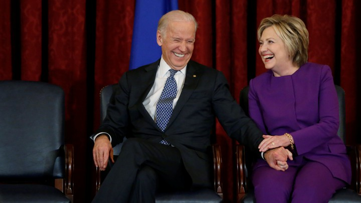 Joe Biden and Hillary Clinton sit on chairs laughing together in front of a red curtain.