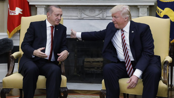 Trump pats Erdoğan on the back during a meeting in the Oval Office.