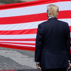 U.S. President Donald Trump stands in front of the American flag.