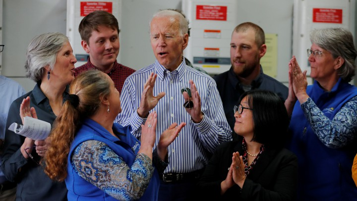 Joe Biden speaks surrounded by a circle of staff members and supporters.