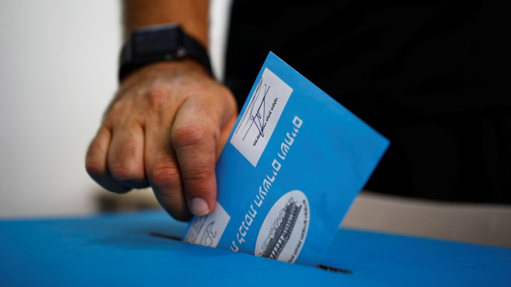 A man's hand is pictured dropping his vote into a ballot box in an Israeli general election.