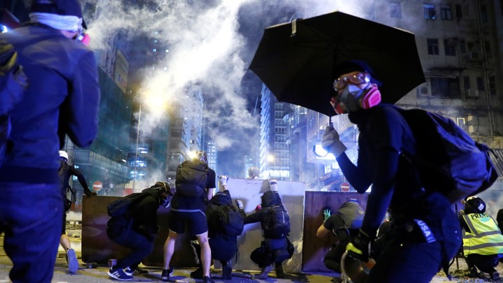 Protesters take cover behind boards during a protest in the Mong Kok area of Hong Kong.