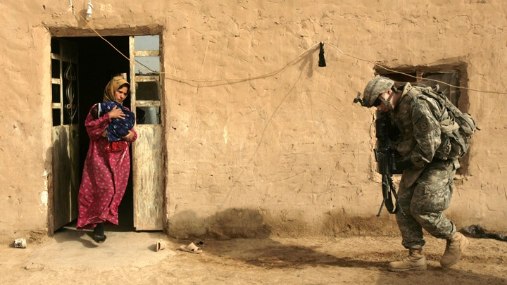 An Iraqi woman, carrying a newborn infant, leaves her home as a U.S. Army soldier prepares to search the house.