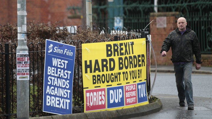 "A man walks past posters reading ""Brexit Hard Border Brought to You By Tories, DUP"" and ""West Belfast Stands Against Brexit."""