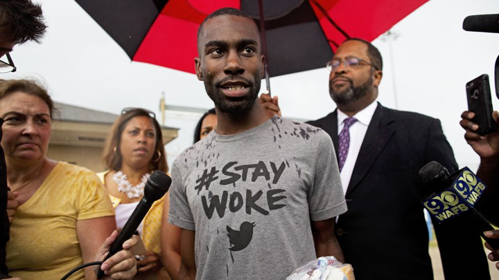 DeRay Mckesson speaks to the media, wearing a grey shirt that says 'Stay Woke.'
