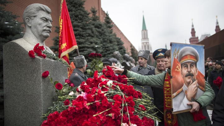 A woman holding a portrait of Stalin places flowers near the monument signifying Joseph Stalin's grave near the Kremlin wall to mark the anniversary of Stalin's birth.