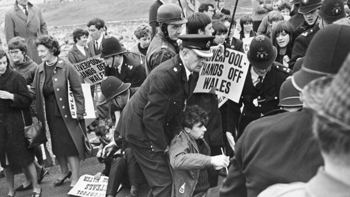 "Welsh-nationalist demonstrators holding signs that read ""Liverpool—hands off Wales"" are dragged away by police officers."