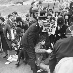 """Welsh-nationalist demonstrators holding signs that read """"Liverpool—hands off Wales"""" are dragged away by police officers."""