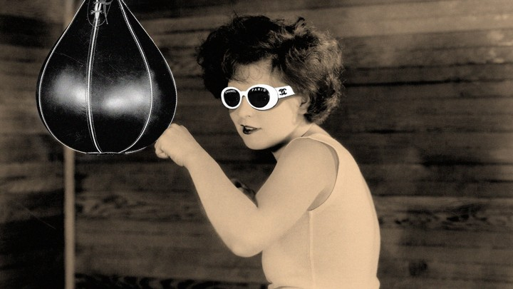 """A woman in """"clout goggles"""" (white sunglasses) hits a punching bag."""