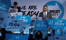 """Nigel Farage speaks to Brexit Party supporters who hold signs reading """"I am ready."""""""