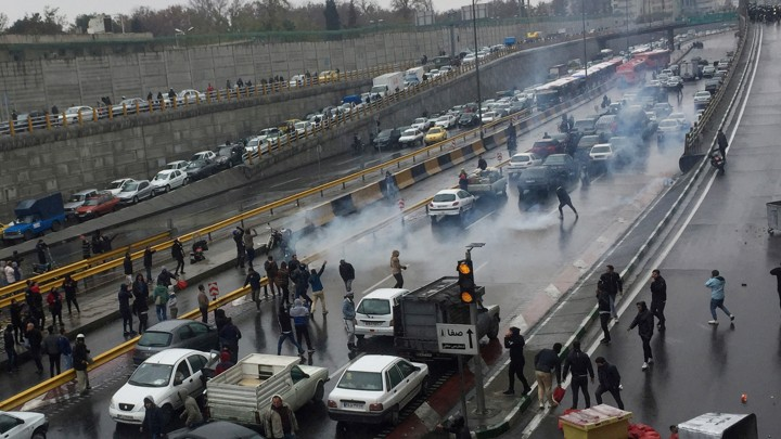 People park their cars on a crowded highway in Tehran to protest rising gas prices.