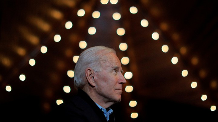 Joe Biden looks up at the ceiling, surrounded by small lights.