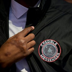 Norman Brown, a credible messenger who spent 22 years in federal prison and is now employed by the Department of Youth Rehabilitation Services, shows off his jacket.
