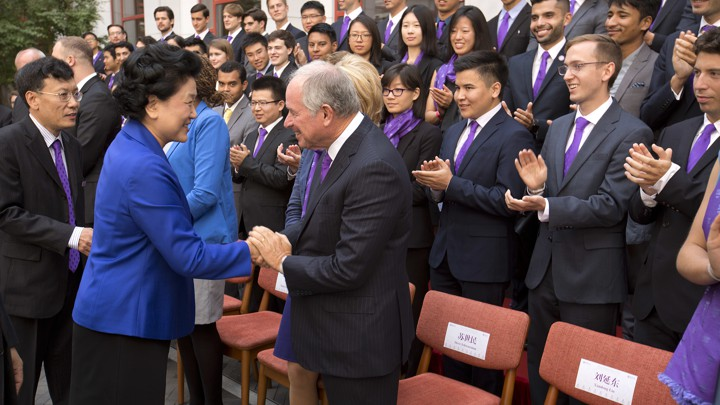 Liu Yandong shakes hands with Stephen Schwarzman as the first class of Schwarzman scholars applaud.