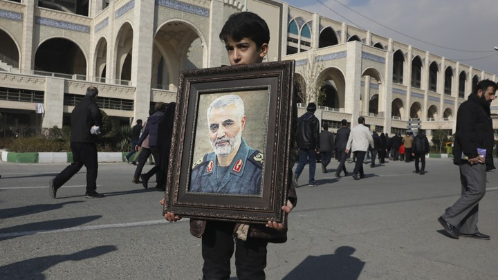 A boy carries a portrait of the Iranian Revolutionary Guard Corps general Qassem Soleimani.