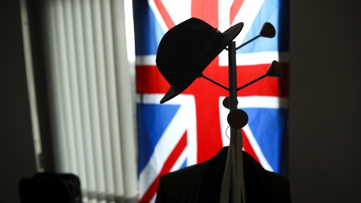 An image of a hat hanging on a hook in front of the Union Jack flag.