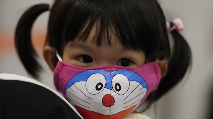 A young passenger wears a face mask as she waits at the immigration counter in Malaysia.