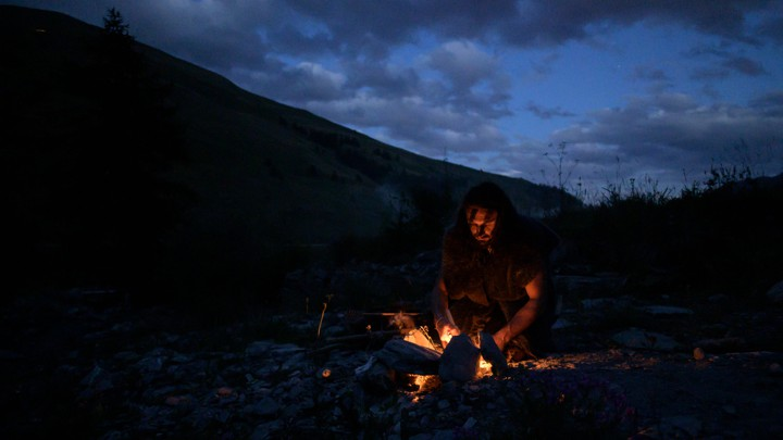 A man dressed in archaic clothes starts a fire in the dark.