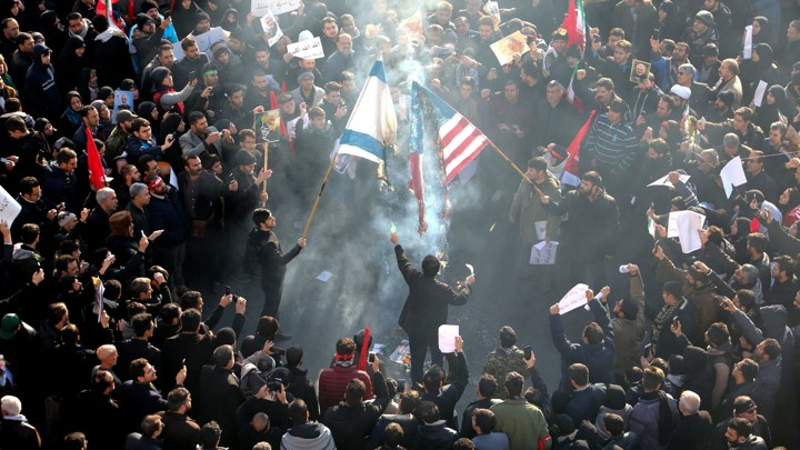 Iranians set a U.S. and an Israeli flag on fire during a funeral procession organized to mourn the slain military commander Qassem Soleimani.
